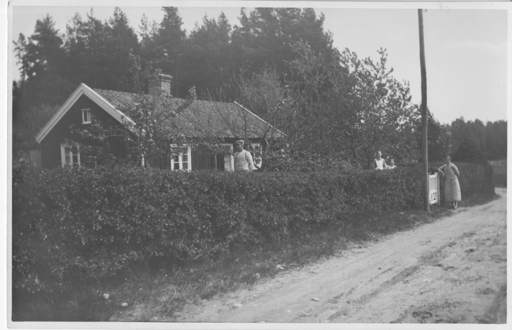 The cottage. Karl, Karolina, and daughter Svea are seen standing behind the hedge. The woman at the gate is unknown.